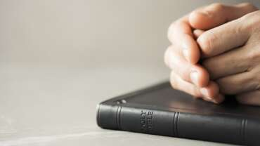 Hands closed in prayer on Holy Bible. Christian banner with copy space. Prayer and gospel spreading